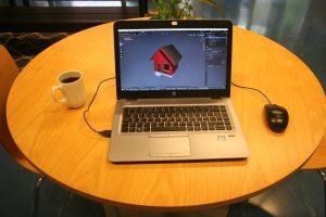 Kahvikupin vieressä kannettavalla tietokoneella on auki 3D-mallinnus.